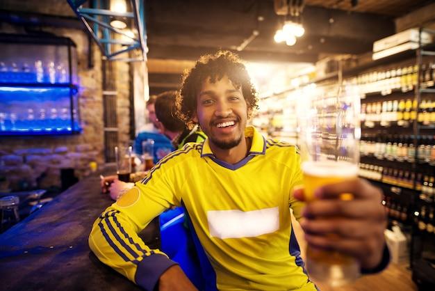 Fã de futebol alegre está saudando em nome da vitória de suas equipes em um pub.