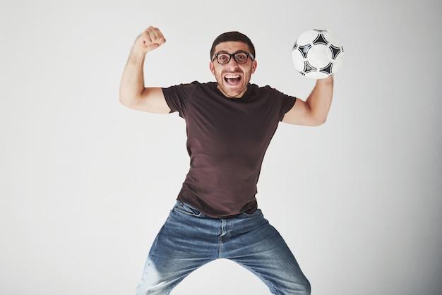 Fã de futebol animado com uma bola de futebol isolada no branco
