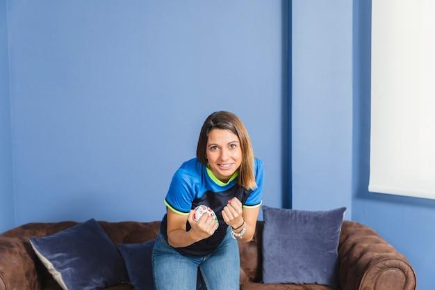 Fã de futebol feminino feliz no sofá