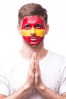 Fã de futebol jovem espanhol com gesto de orar isolado na parede branca