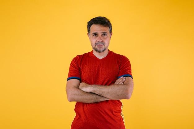 Fã de futebol vestindo camisa vermelha posa com os braços cruzados