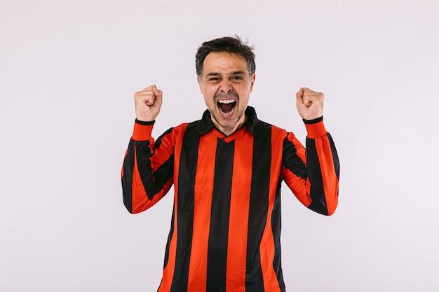 Fã de futebol vestindo uma camisa listrada preta e vermelha, cerrou os punhos e gritou torcendo por seu time no fundo branco
