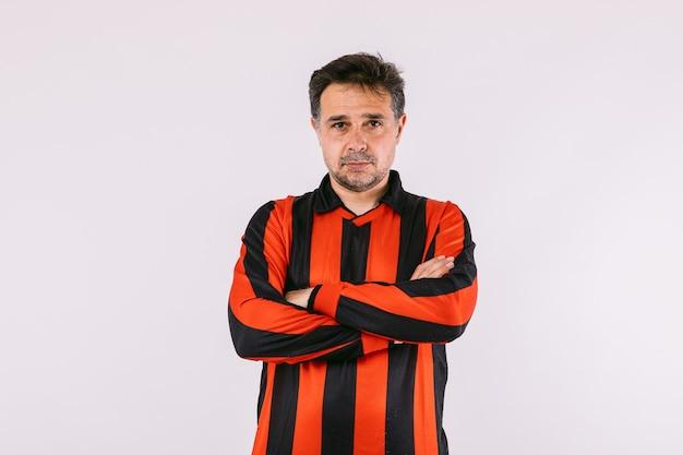 Fã de futebol vestindo uma camisa listrada preta e vermelha posa com os braços cruzados sobre um fundo branco