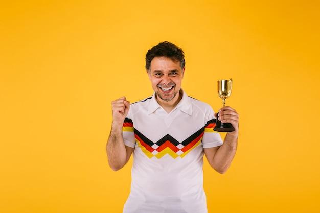 Fã de futebol vestindo uma camiseta branca com listras pretas, vermelhas e amarelas, ele fecha o punho e segura um troféu de vencedor.