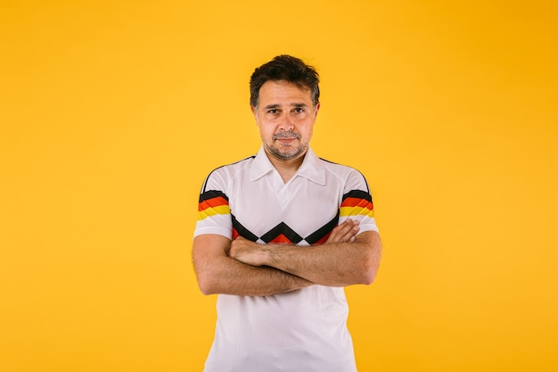 Fã de futebol vestindo uma camiseta branca com listras pretas vermelhas e amarelas posa com os braços cruzados