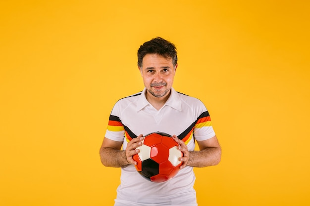 Fã de futebol vestindo uma camiseta branca com listras pretas, vermelhas e amarelas, segura uma bola nas mãos