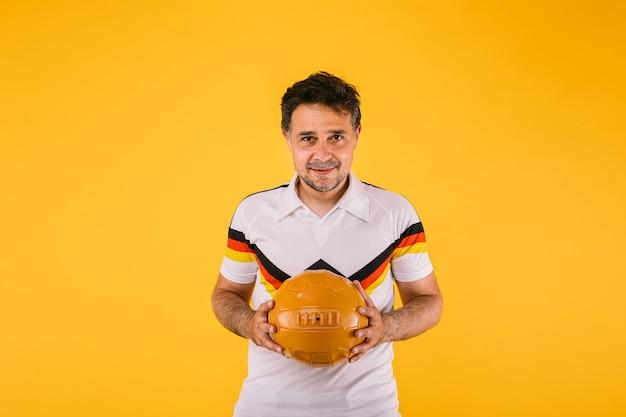 Fã de futebol vestindo uma camiseta branca com listras pretas, vermelhas e amarelas, segura uma bola retrô nas mãos