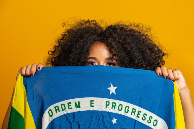Fã de mulher negra misteriosa segurando uma bandeira do brasil na sua cara. cores do brasil na parede amarela,