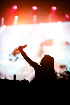 Fã de música curtindo a performance noturna de uma artista famosa no palco e usando seu smartphone