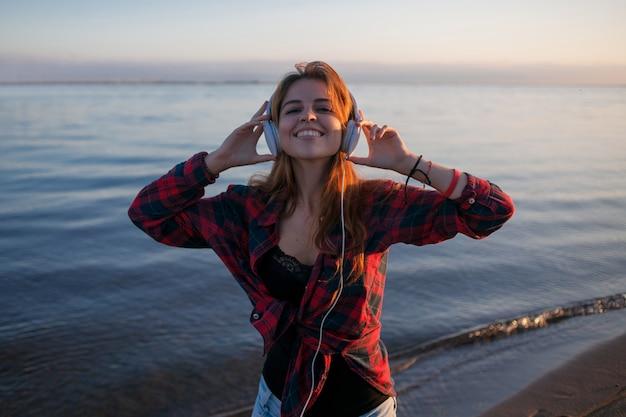 Fã de música feminina linda jovem. dançando e ouvindo música em fones de ouvido.