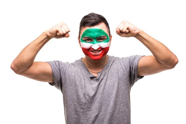 Fã de partidário de homem bonito da equipe nacional do irã pintada com o rosto da bandeira obter a vitória feliz gritando para a câmera. emoções dos fãs.