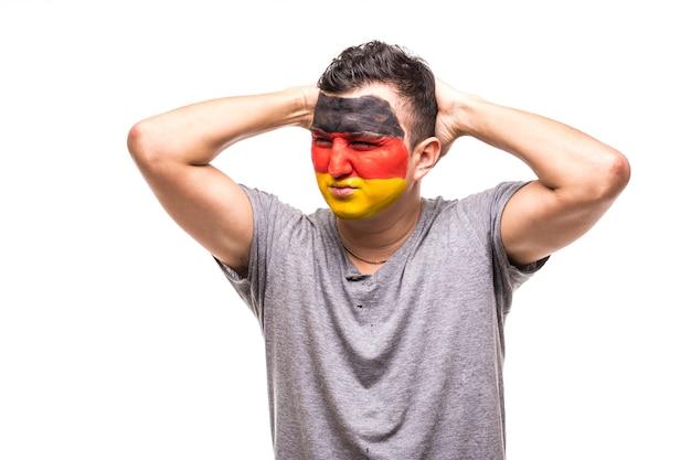 Fã de torcedor do homem bonito da equipe nacional da alemanha pintou o rosto da bandeira obter emoções tristes e frustradas infelizes em uma câmera. emoções dos fãs.