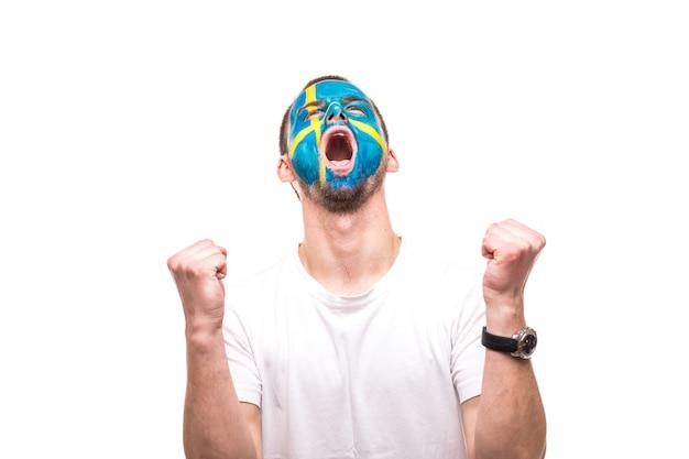 Fã de torcedor do homem bonito da seleção da suécia com a cara da bandeira pintada obter a vitória feliz gritando para a câmera. emoções dos fãs.