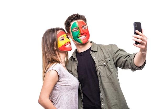 Fã de torcedor homem bonito da seleção nacional de portugal pintada com cara de bandeira tomar selfie com torcedor mulher fã da seleção espanhola. emoções dos fãs.
