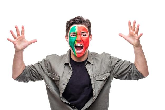 Fã de torcedor homem bonito da seleção nacional de portugal pintou o rosto da bandeira obter vitória feliz gritando para a câmera. emoções dos fãs.