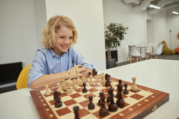 Fã de xadrez motivado, menino caucasiano, parecendo animado enquanto jogava xadrez, sentado à mesa no