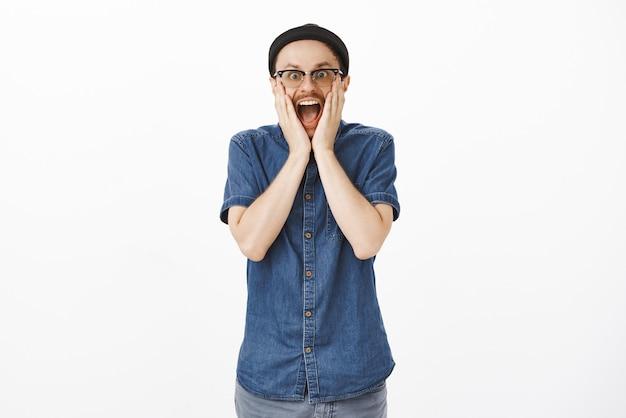 Fã fascinado do sexo masculino assistindo ao show legal gritando de surpresa e empolgação de mãos dadas no rosto, deixando cair o queixo e sorrindo, olhando com entusiasmo e espanto