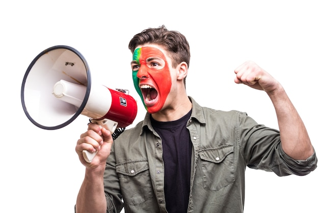Fã leal de torcedor homem bonito da seleção nacional de portugal pintou o rosto da bandeira obter vitória feliz gritando no megafone com a mão pontuda. emoções dos fãs.