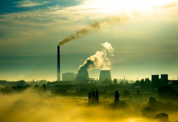 Fábrica com tubos e fumaça ao amanhecer do pôr do sol. paisagem urbana vermelha e laranja. paisagem com fumaça e névoa da manhã. contrastando com a silhueta escura da planta