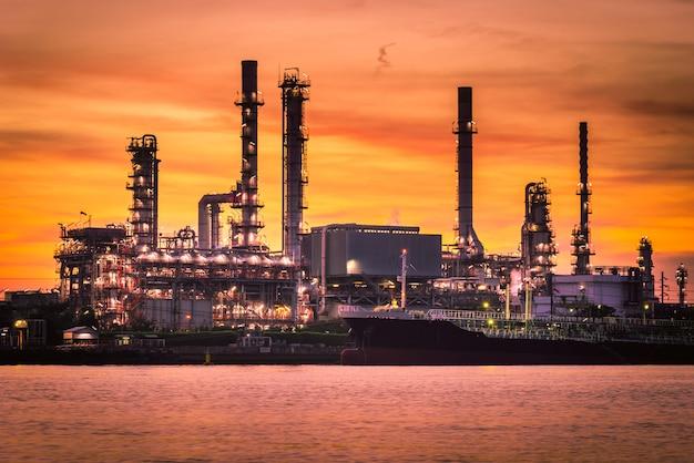 Fábrica da refinaria do petróleo e do gás com o céu bonito no nascer do sol.