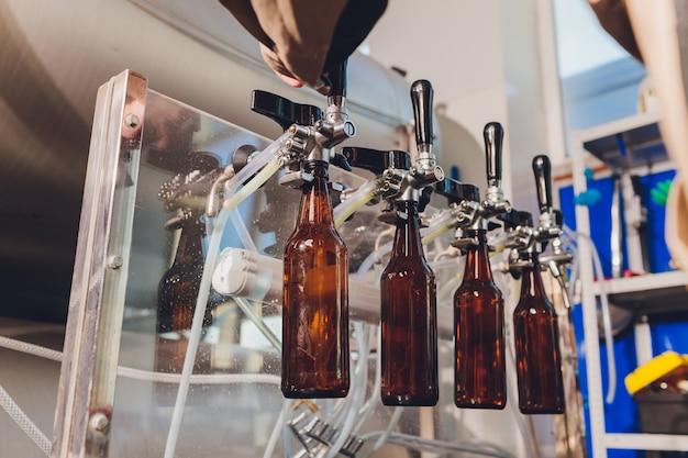 Fábrica de cervejaria derramando cerveja em garrafas de vidro nas linhas transportadoras. trabalho industrial, produção automatizada de alimentos e bebidas. trabalho tecnológico na fábrica.