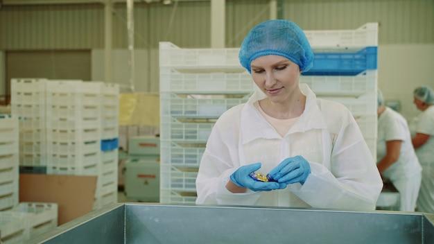 Fábrica de doces. operário que verifica a máquina de embalagem.