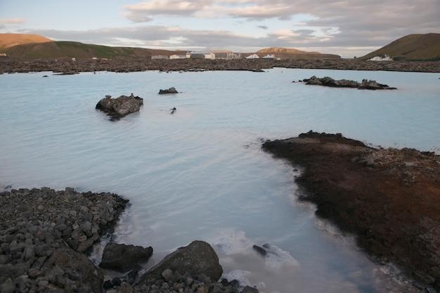 Fábrica de energia geotérmica, rodeada por uma paisagem rochosa com um lago