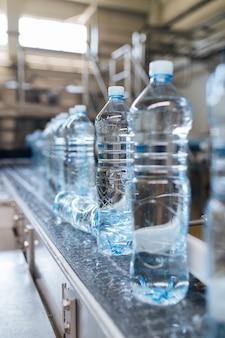 Fábrica de engarrafamento - linha de engarrafamento de água para processamento e engarrafamento de água pura em garrafas azuis. foco seletivo.
