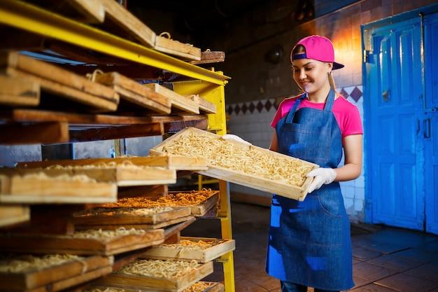 Fábrica de macarrão. produção de espaguete. massa crua. trabalhador com uma caixa de macarrão. menina trabalha na produção de macarrão