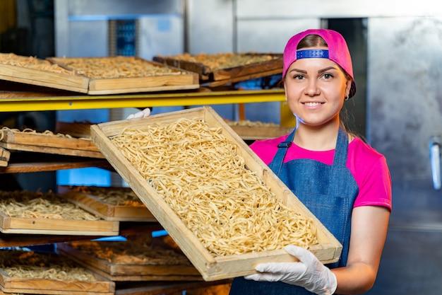 Fábrica de massas e etapas de produção de massas. macarrão fresco cortado em caixas nas prateleiras. máquina industrial.