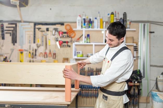 Fábrica de móveis, pequenas empresas, conceito de negócio - homem trabalhador na produção de móveis