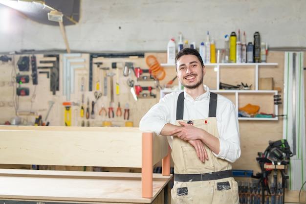 Fábrica de móveis, pequenas empresas, conceito de negócio - homem trabalhador na produção de móveis.