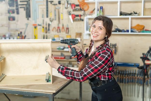 Fábrica de móveis, pequenas empresas e conceito de mulher trabalhadora - mulher com uma broca no
