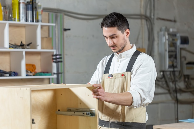 Fábrica de móveis, pequenas empresas e conceito de pessoas - jovem trabalhador trabalha em fábrica