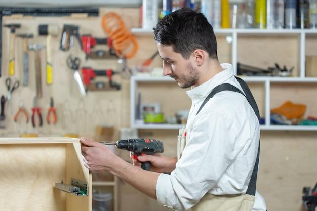 Fábrica de móveis, pequenas empresas e conceito de pessoas - jovem trabalhador trabalha em uma fábrica de produção de móveis.