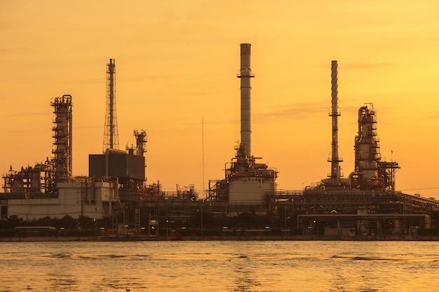 Fábrica de refinaria de petróleo em silhueta e céu do nascer do sol