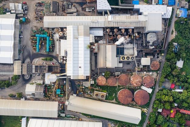 Fábrica industrial fabricando cana e melaço com emissão de fumaça das chaminés