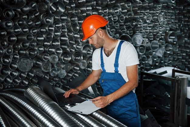 Fabricação moderna. homem de uniforme trabalha na produção. tecnologia industrial moderna.