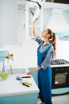 Fabricante de móveis femininos bonitos no armário de reparo de uniforme na cozinha. handywoman corrigindo problema com armário de garniture, serviço de conserto em casa