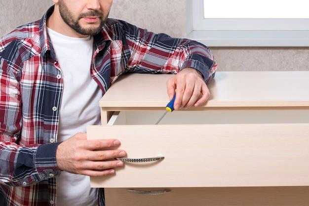 Fabricante de móveis masculino monta móveis em um apartamento