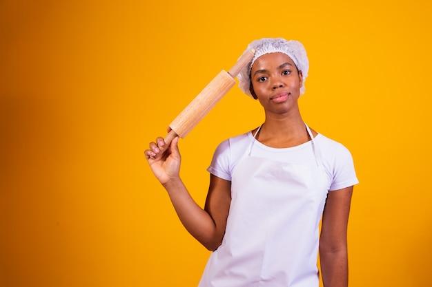 Fabricante de pizza jovem em fundo amarelo, segurando o rolo de massa.