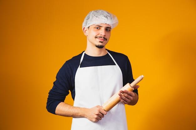 Fabricante de pizza jovem rapaz em fundo amarelo, segurando o rolo de massa.