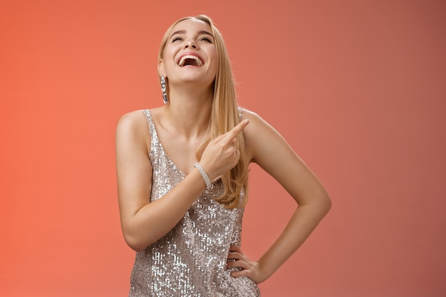 Fabulosa despreocupada mulher loira atraente em prata vestido de festa de noite rindo alto divirta-se, levante a mão com alegria apontando o dedo indicador direito, apreciando o humor incrível, fundo vermelho.