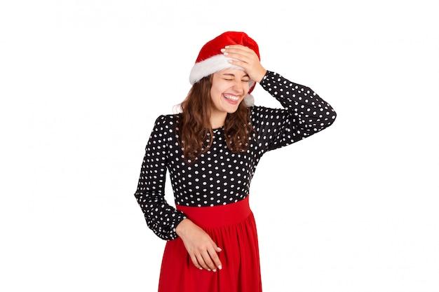 Fabulosa mulher alegre, mostrando a língua e olhando para baixo ri colocar a mão na testa. garota emocional no chapéu de natal papai noel isolado