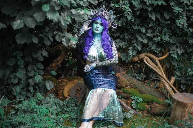Fabulosa sereia escura com pele azul na floresta close up