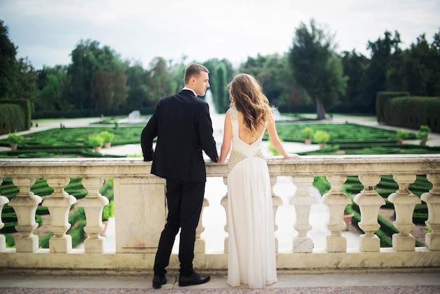 Fabuloso casal de noivos caminhando ao redor do território do castelo em seu dia festivo.