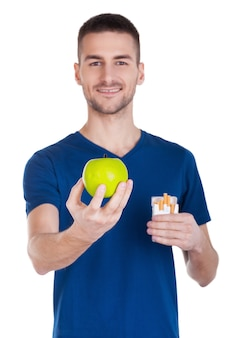 Faça a escolha certa! jovem confiante estendendo a mão com uma maçã enquanto segura o maço de cigarros em outro e isolado no fundo branco