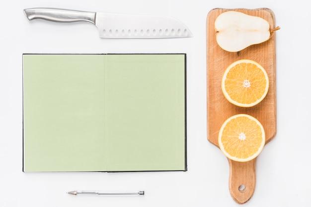 Faca afiada; caderno de páginas em branco; caneta; laranjas cortadas ao meio e pêra em fundo branco