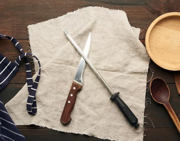 Faca afiada e amolador com cabo em madeira