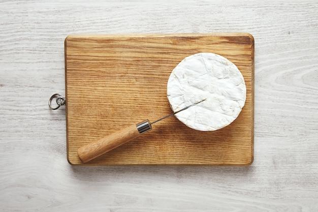 Faca antiquada com cabo de madeira enfiada no queijo camembert na tábua de cortar na mesa de madeira branca envelhecida